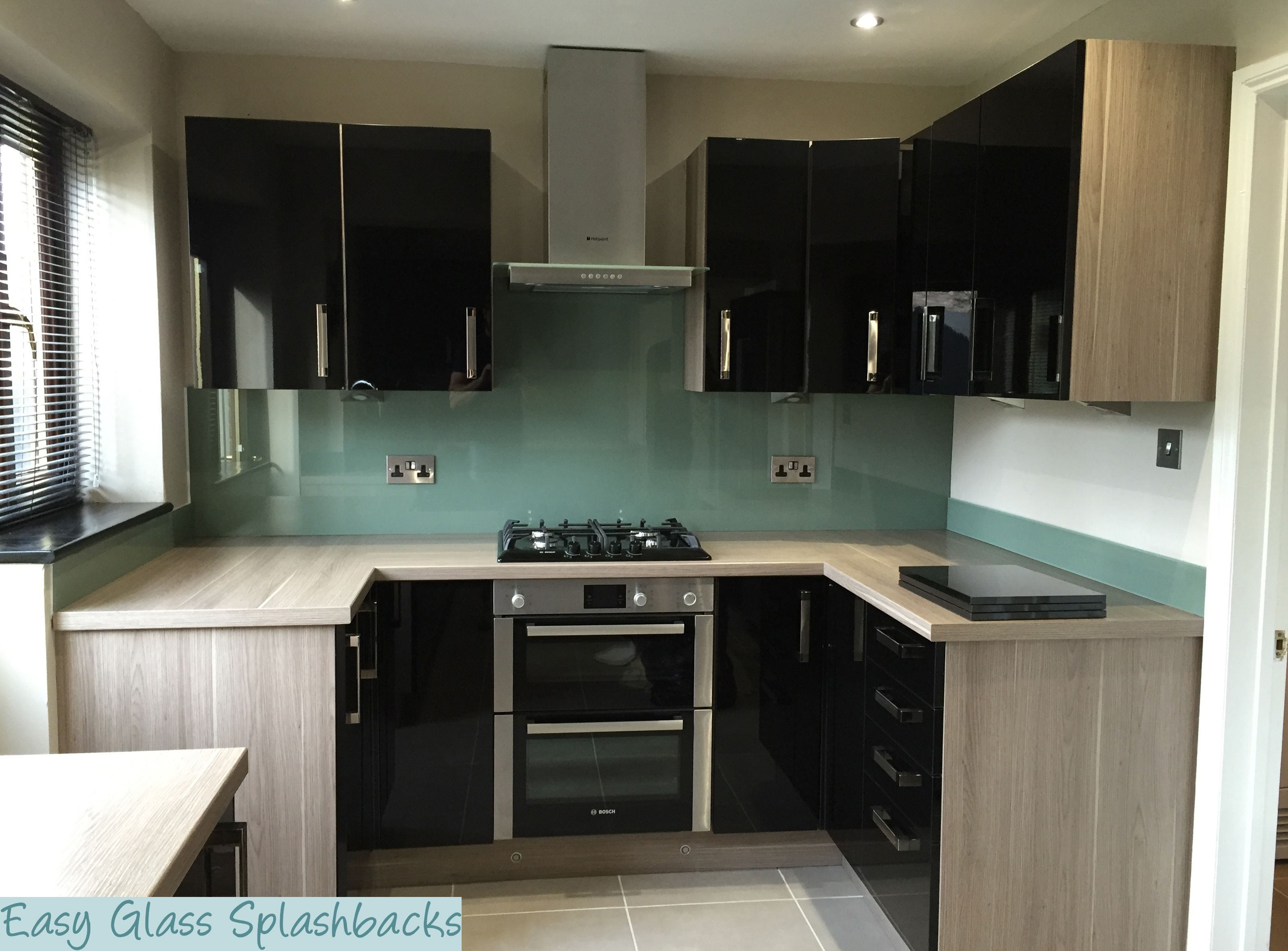 Dulux Tuscan Olive Coloured Glass Splashback In A Black Kitchen With