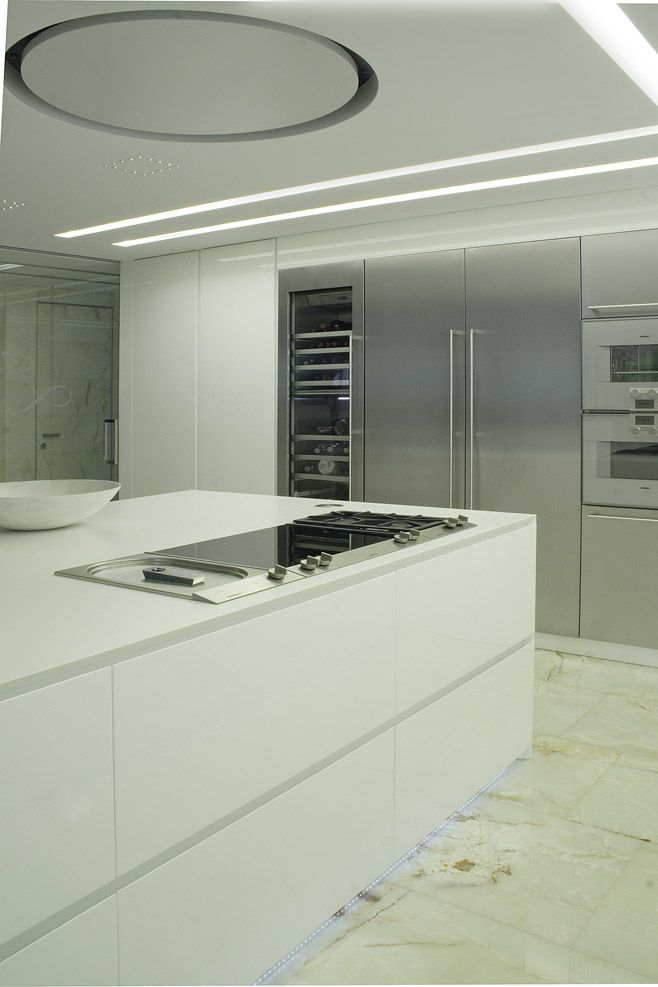 cucina corian design bianco illuminazione led acciaio cappa incasso circolare gaggenau cantina vini isola marmo onice