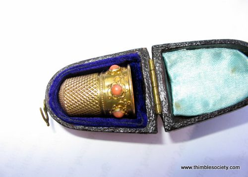 Gold thimble, probably 15/18ct. Set around the skirt with corals in intricate gold cups. English cir 1860. In leather case.