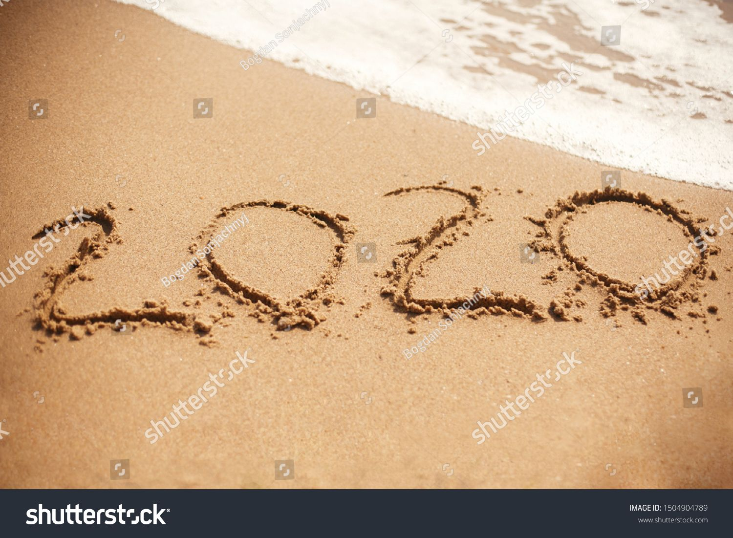 2020 New Year 2020 written on sandy beach with wave foam at sea beach Happy New Year Tropical celebration Inscription on golden sand