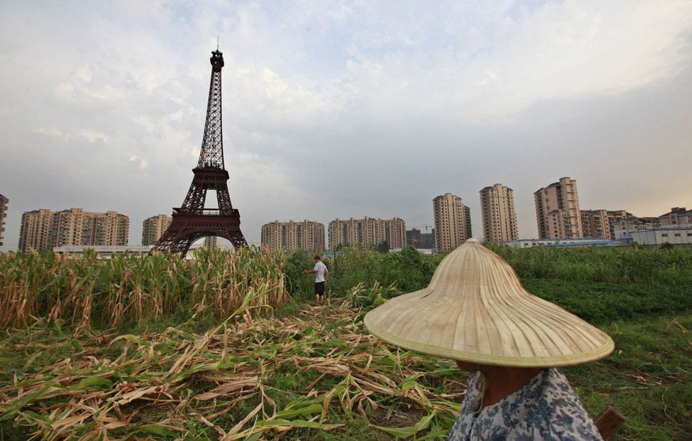 Un agricultor camina a través de un campo, cerca de una réplica de la Torre Eiffel, en Hangzhou, provincia de Zhejiang.