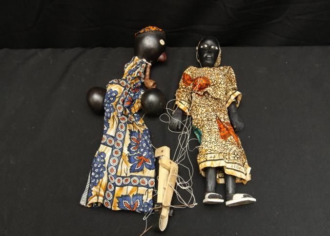 HAND AND STRING PUPPETS. Ghana. (A) Male hand puppet with calabash head and hands, cowrie shell eyes, wood pipe, and colorful wax print cloth. Custom base. H 17in. (B) Female string puppet articulated at shoulders, elbows, waist, hips, and knees. Wears wax print dress and kerchief and white sandals. H 15.5in.