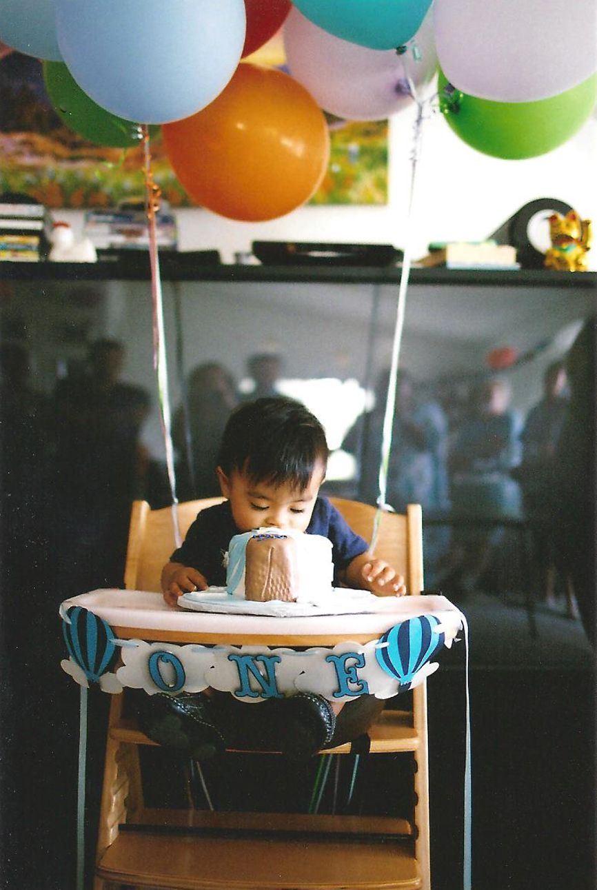 toddler eating birthday cake on high chair photo