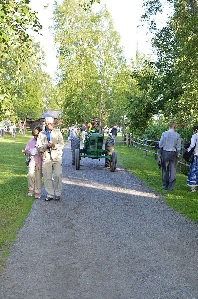 Lapset pääsevät traktoriajelulle. Katselijoille ja ohikulkijoille vilkutetaan iloisesti.