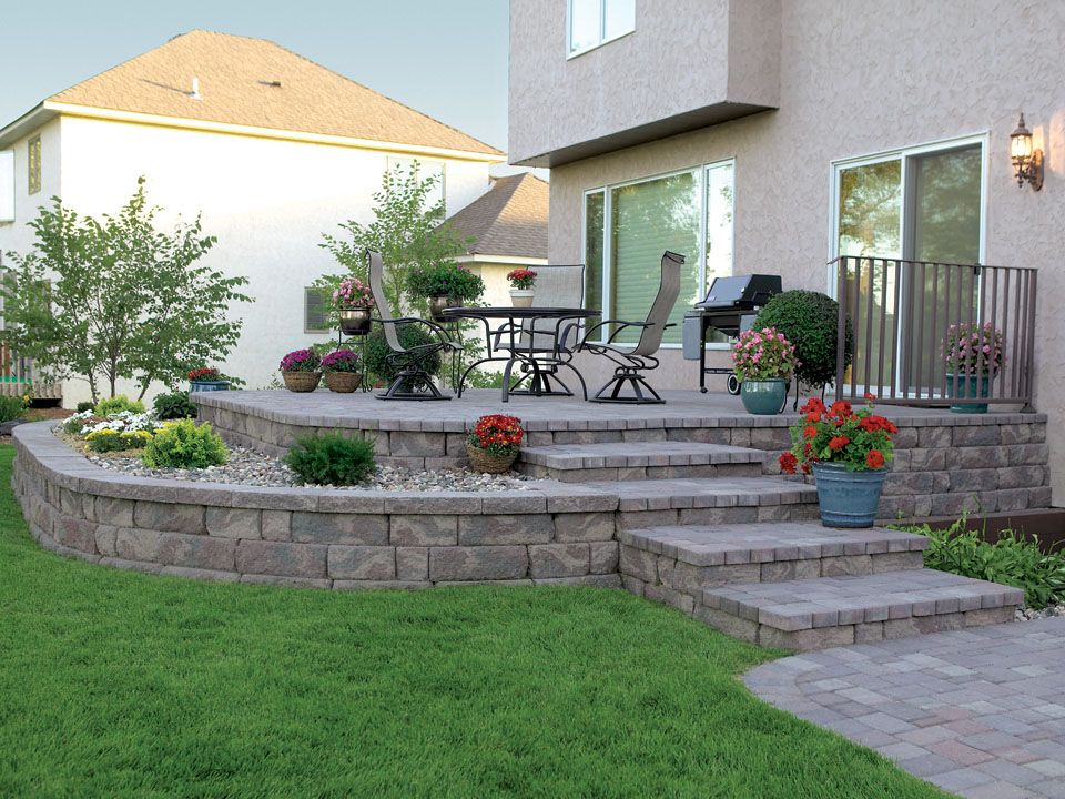 A Raised Patio Featuring The Highland Stone Retaining Wall System Concrete Patio Designs Patio Pavers Design Stone Patio Designs