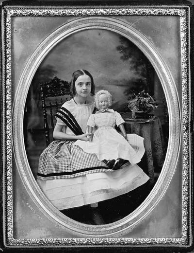 young girl with a wax doll [it could be paper machet,but i think it's wax]