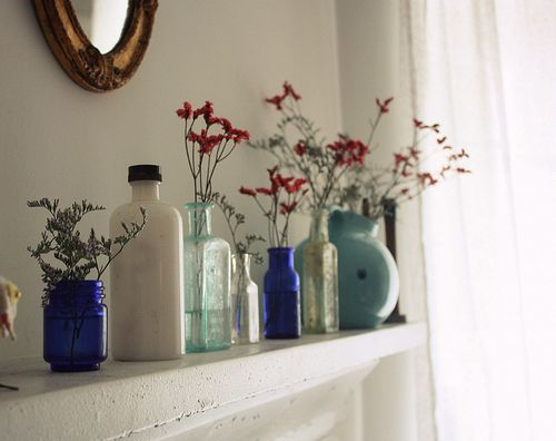 different styles/colors bottles with wild flowers split up between them. love.