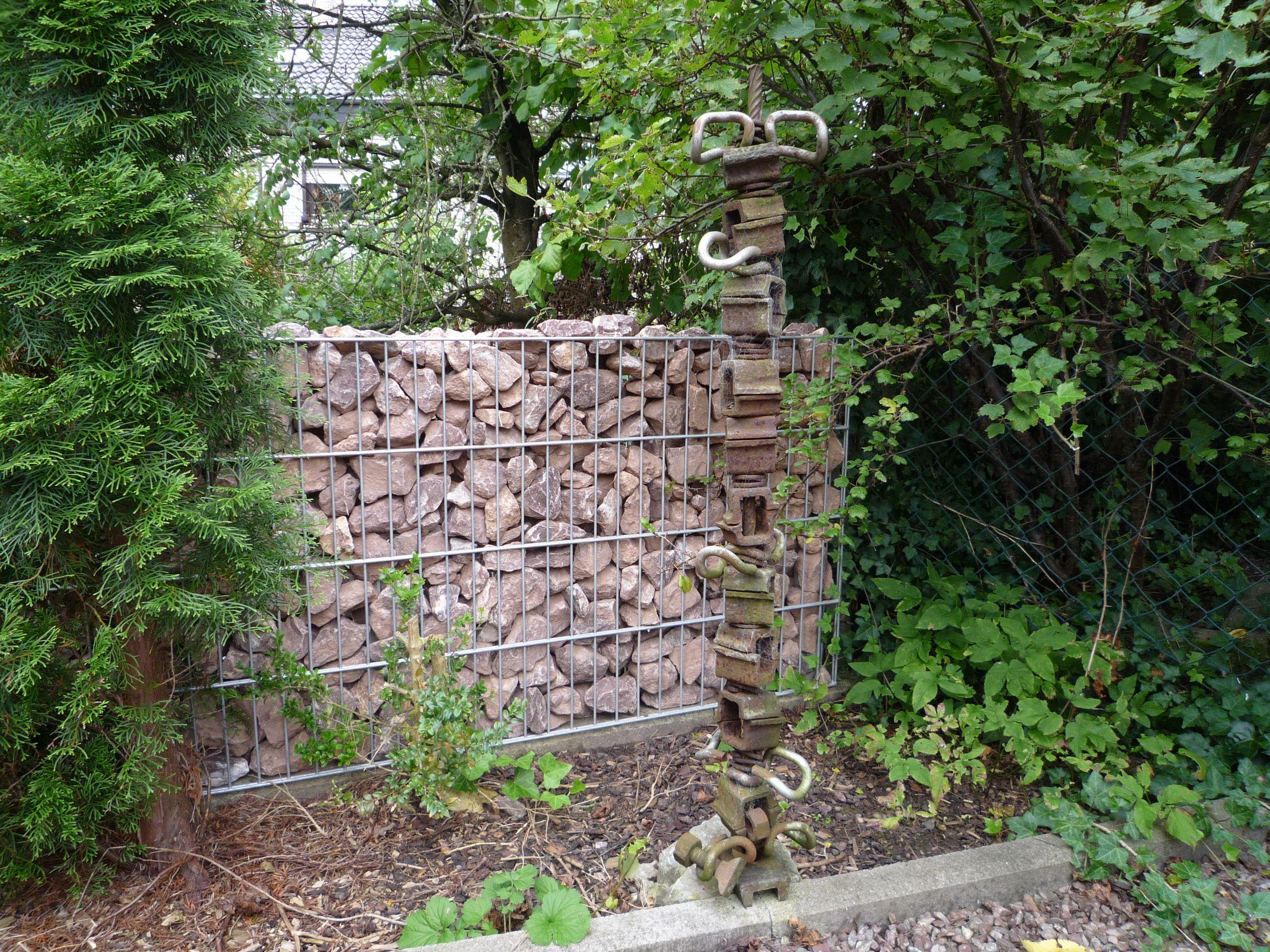 Gabione mit roten Gabionensteinen im Garten