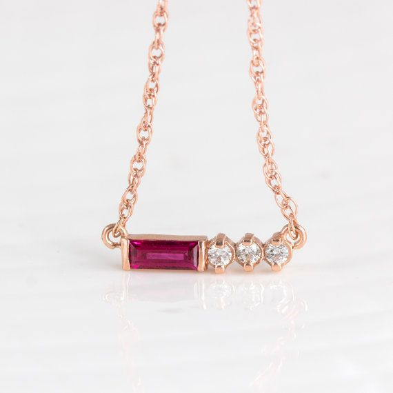 This petite necklace features a beautiful deep pink ruby baguette accented with three sparkling white diamonds. The settings, chain, and necklace clasp are crafted from solid 14k rose gold, and can be finished with your choice of a bright polish or brushed matte finish (photos show a bright polish finish). This necklace is perfect for layering with others, or wearing alone for a simple, minimalist look. ♡Ruby is the birthstone for the month of July, and diamond is the birthstone for the…