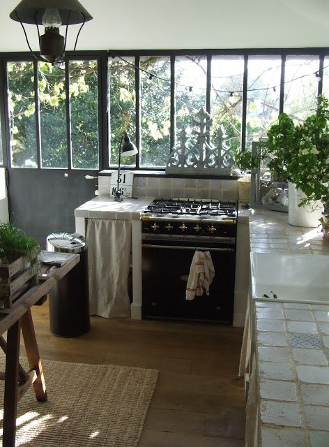 French kitchen. I love the tiles on the counter, the large white sink, the windows, the greenery on the counter...