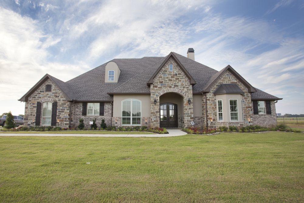 Home elevation with stucco brick and stone including a for Exterior home accents