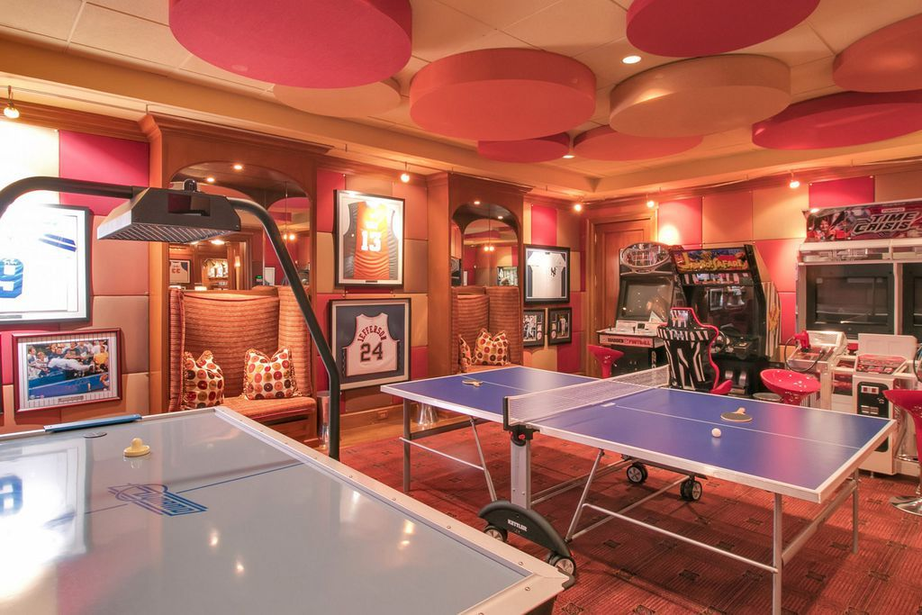 This Game Room Boasts Multiple Arcade Games And A Table Tennis Set Surrounded By Stylish Walls That Match The Cei Arcade Room Game Room Family Game Room Design