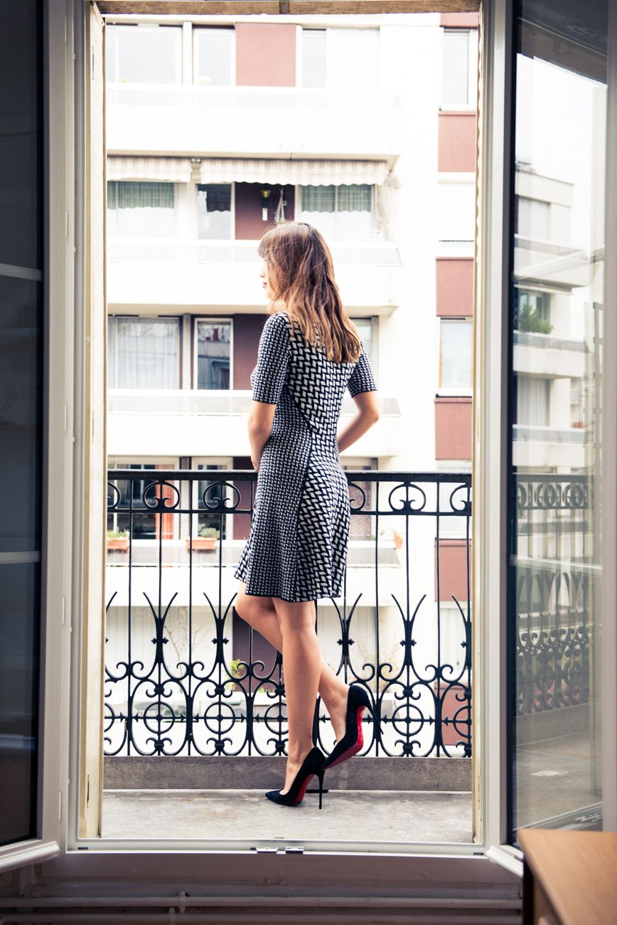 Can't go wrong with above the knee length black and white patterned knit dress and classic black pumps.