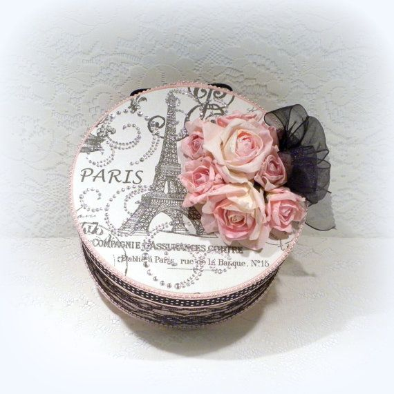 Elegant Paris inspired gift or storage box in pink fabric that I covered with black lace. The lid is covered in French script, Eiffel Tower and post marked fabric. Embellished with black and white polka dot grosgrain ribbon, rhinestones, pink parchment paper roses and black sheer wired ribbon. The inside is white. Measures 8 1/2 diameter x 6 high which includes the roses and ribbon. Ready to ship