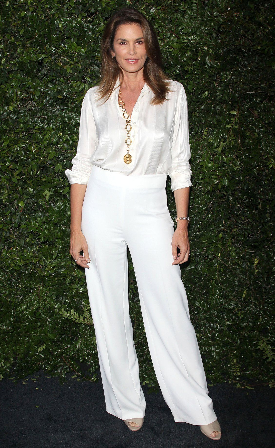 9ad547ff185be Cindy Crawford in a white silk blouse tucked into wide leg pants