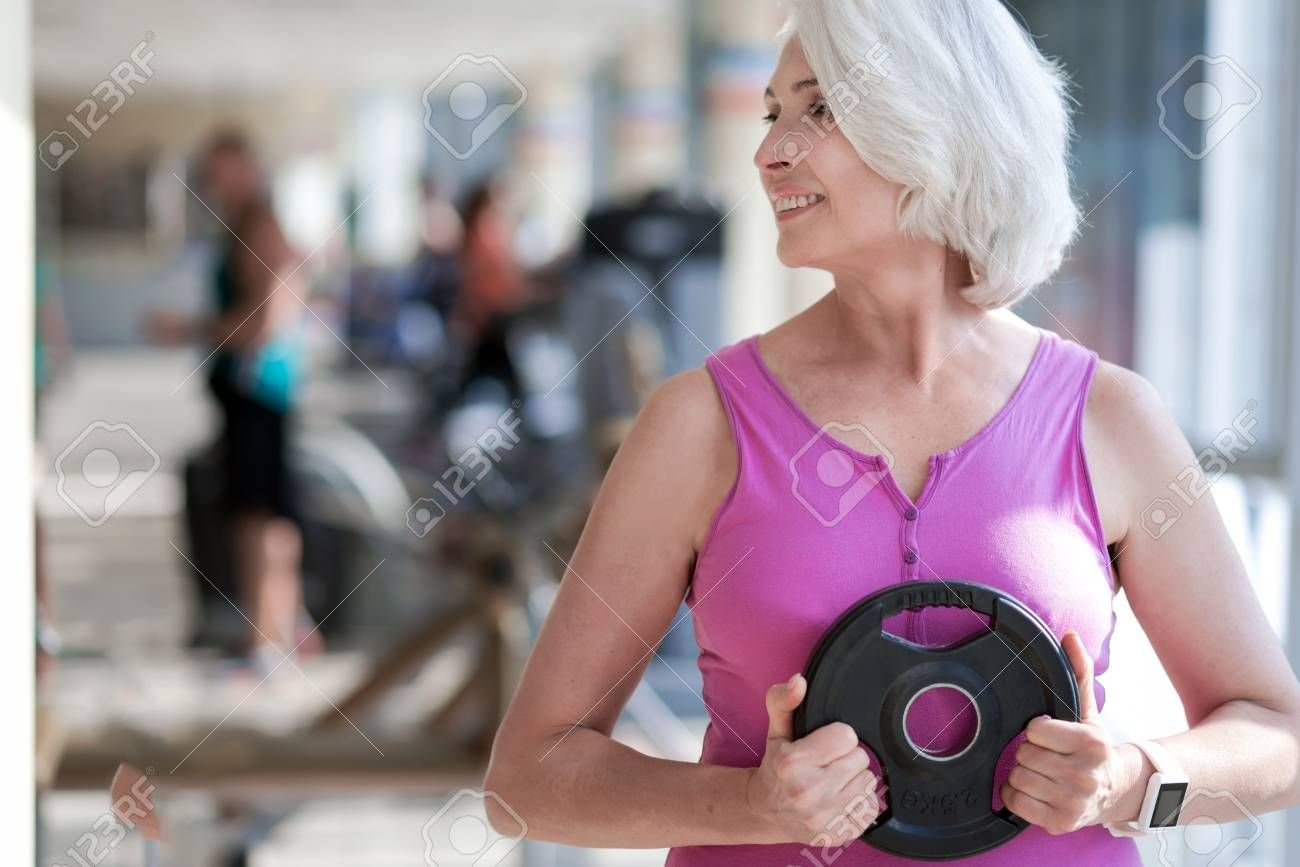 Happy fitness. Beautiful active woman turning head and smiling while exercising with plate in a gym....