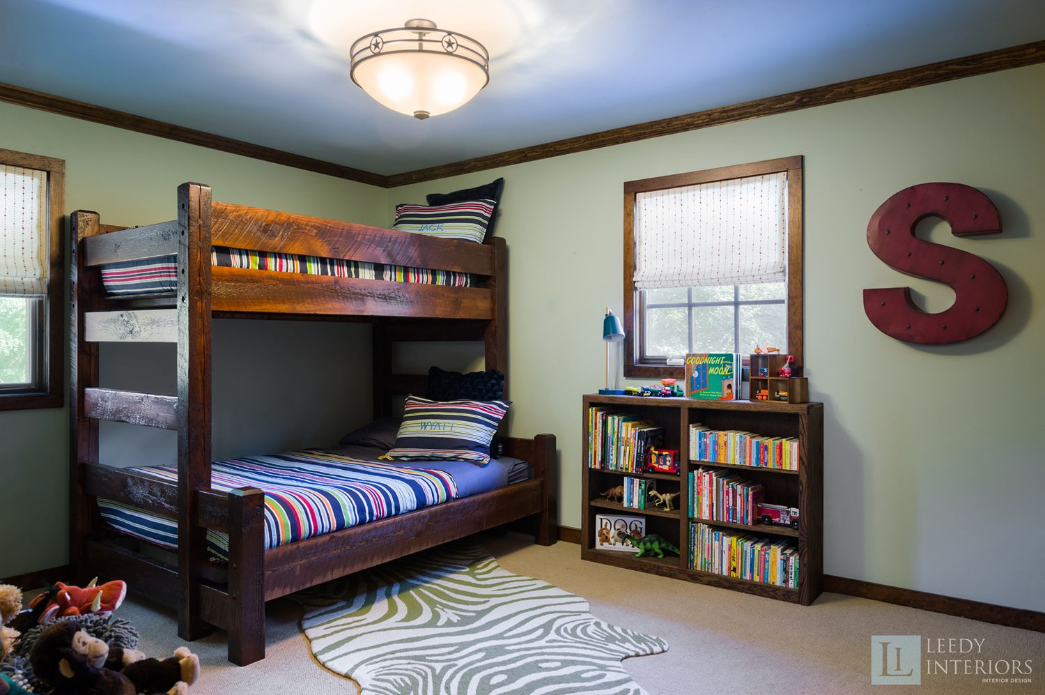 We designed this bedroom for 2 young boys who absolutely love animals, who doesn't? The boys needed a place to store their abundance of stuffed animals and custom open top storage bins were the perfect solution. We balanced the hardness and weight of the wood in the room with fabric roman shades, soothing paint colors and an area rug. The area rug and window treatments also add subtle texture to the room. www.leedyinteriors.com