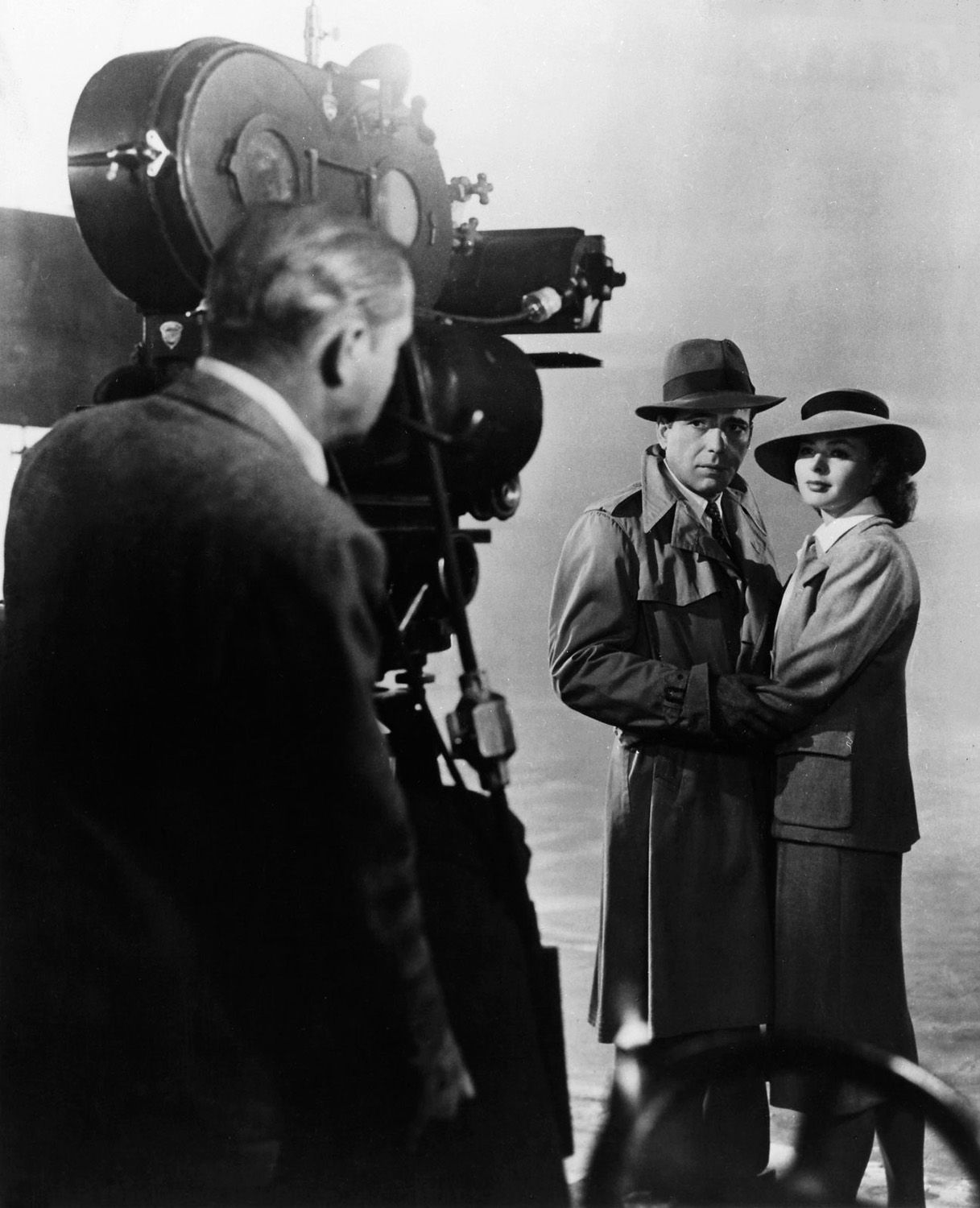 "This is a rare image from behind the camera on the set of CASABLANCA, showing cinematographer Arthur Edeson and stars Humphrey Bogart and Ingrid Bergman (1942). Edeson filmed Ms. Bergman primarily from her left side, using a gauze filter to soften her image, and he placed lights about the set to help catch the sparkle of her eyes. The end result was that Bergman's character came off ""sad, tender and nostalgic"". Film noir lighting was used throughout, but is especially noticeable toward the…"