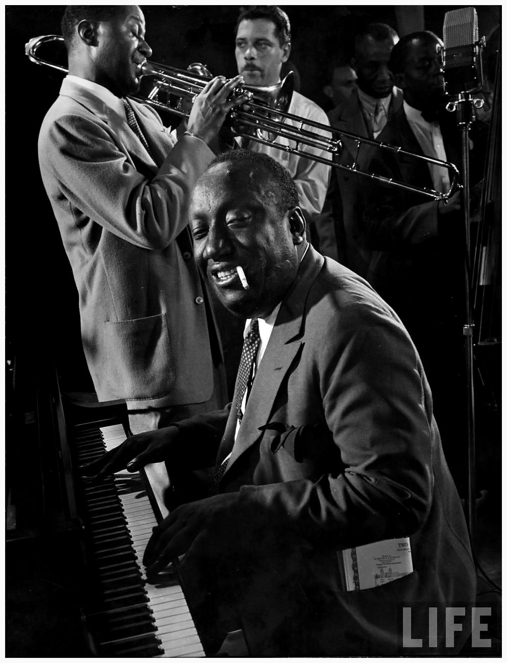 Very good of James P. Johnson at piano as Wilbur De Paris plays trombone, unident. others in bkgrnd. during jam session in studio of LIFE photographer Gjon Mili 1943 NYC