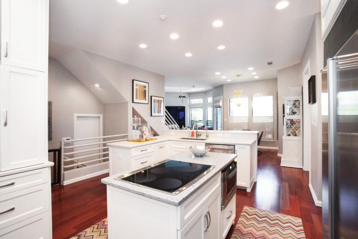 The first level also contains a large family room; an office/study with built-ins; an en-suite bedroom (currently used as a fitness room); and a master suite featuring his-and-hers closets and an oversized bath with a jetted tub, separate vanities, and a walk-in shower.