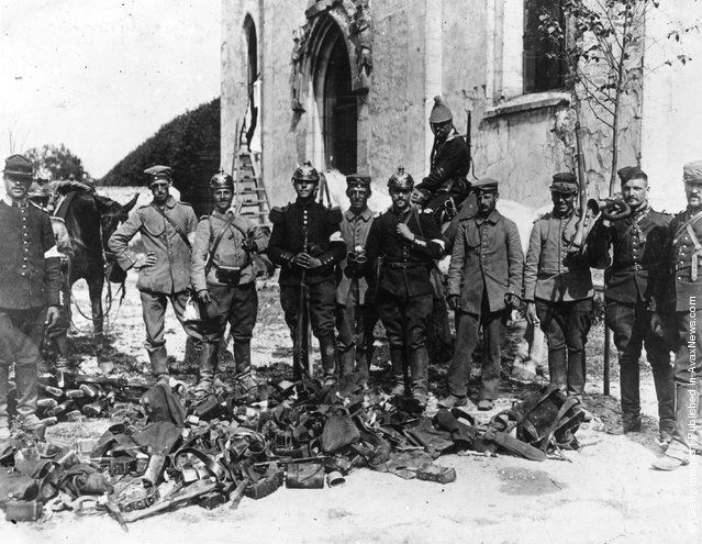 French soldiers wearing German helmets stand with equipment ...