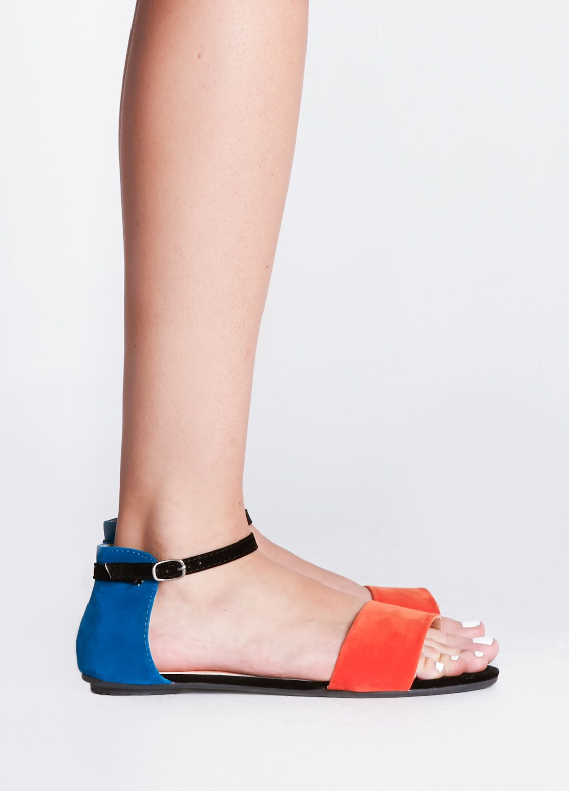 Black faux suede flat sandal featuring orange and blue contrast details. Ankle strap with buckle closure.