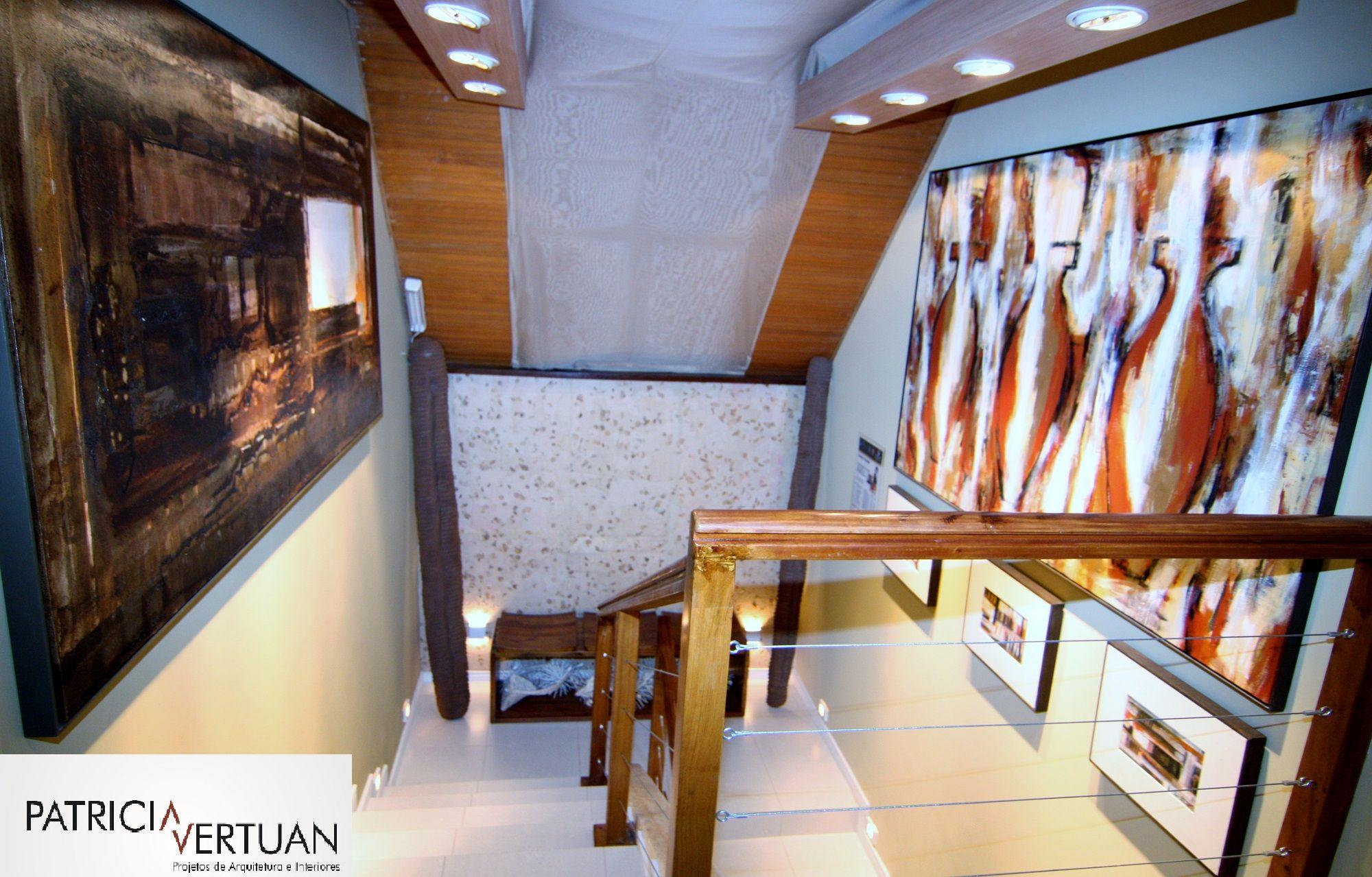 Escada com piso em porcelanato, guarda corpo e corrimão feito em madeira e cabos de aço. Forro em madeira e aplicação de tecido.