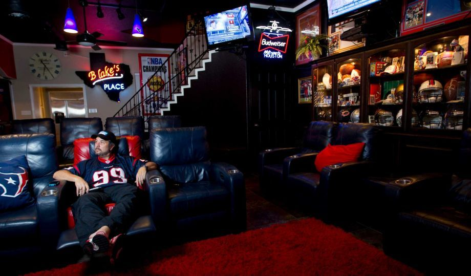 Blake Barnes, a Texans fan, stands in his man cave that