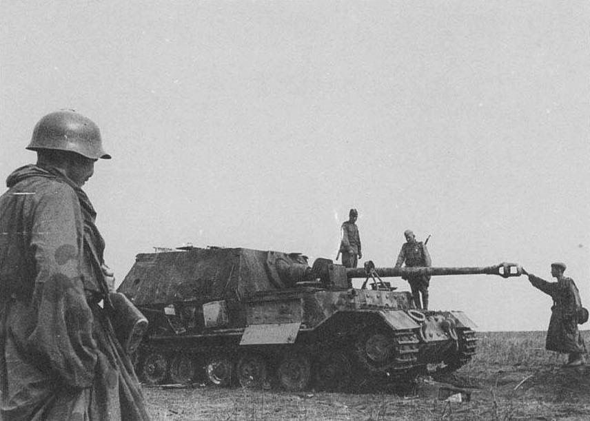 A Russian soldier connects with the sheer power of the Pak 43 on a burnt out Ferdinand at Kursk - 1943.