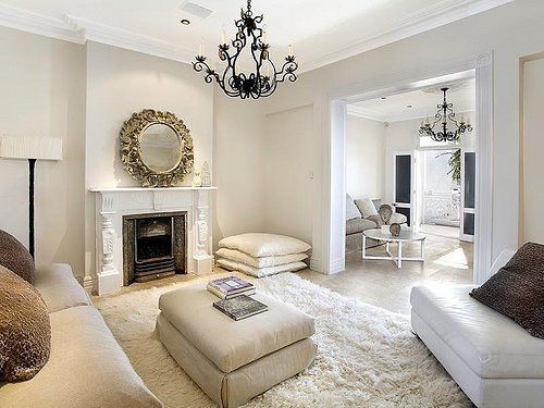 Black chandelier in an all white living roomOff-white walls with cream flokati rug and white furniture! beige sand paint wall color room space. metal black floor lamp with whit shade, ornate round mirror over fireplace, floor pillows and upholstered