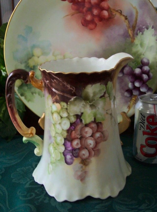 Limoges porcelain hand painted water pitcher with GRAPES! The colorful grapes and foliage are painted on both sides by the artist. The original mold has raised detail and a ruffled foot. The top scalloped edge is gilded. There is very light gild wear at the top edge. It is marked with the Haviland Limoges France Mark 12, this dates it 1894 to 1931.