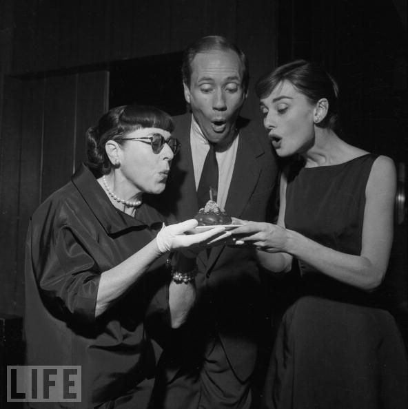 Edith Head, Mel Ferrer, and Audrey Hepburn blow out the candle on Head's birthday cake at a party at the Beverly Hills Hotel in 1955.Photo by Darlene Hammond