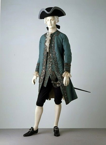 This is part of a court suit from 1760-70 in the V  It doesn't say, but I believe that the matching breeches are missing.  Although this looks acceptable to our modern eyes, I think the black breeches are just so our gentleman model wouldn't be pantless ;-D.