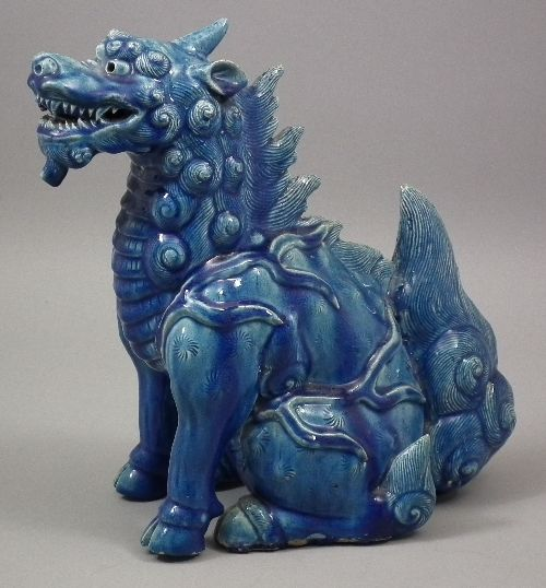 A Chinese blue glazed pottery figure of a seated dragon.