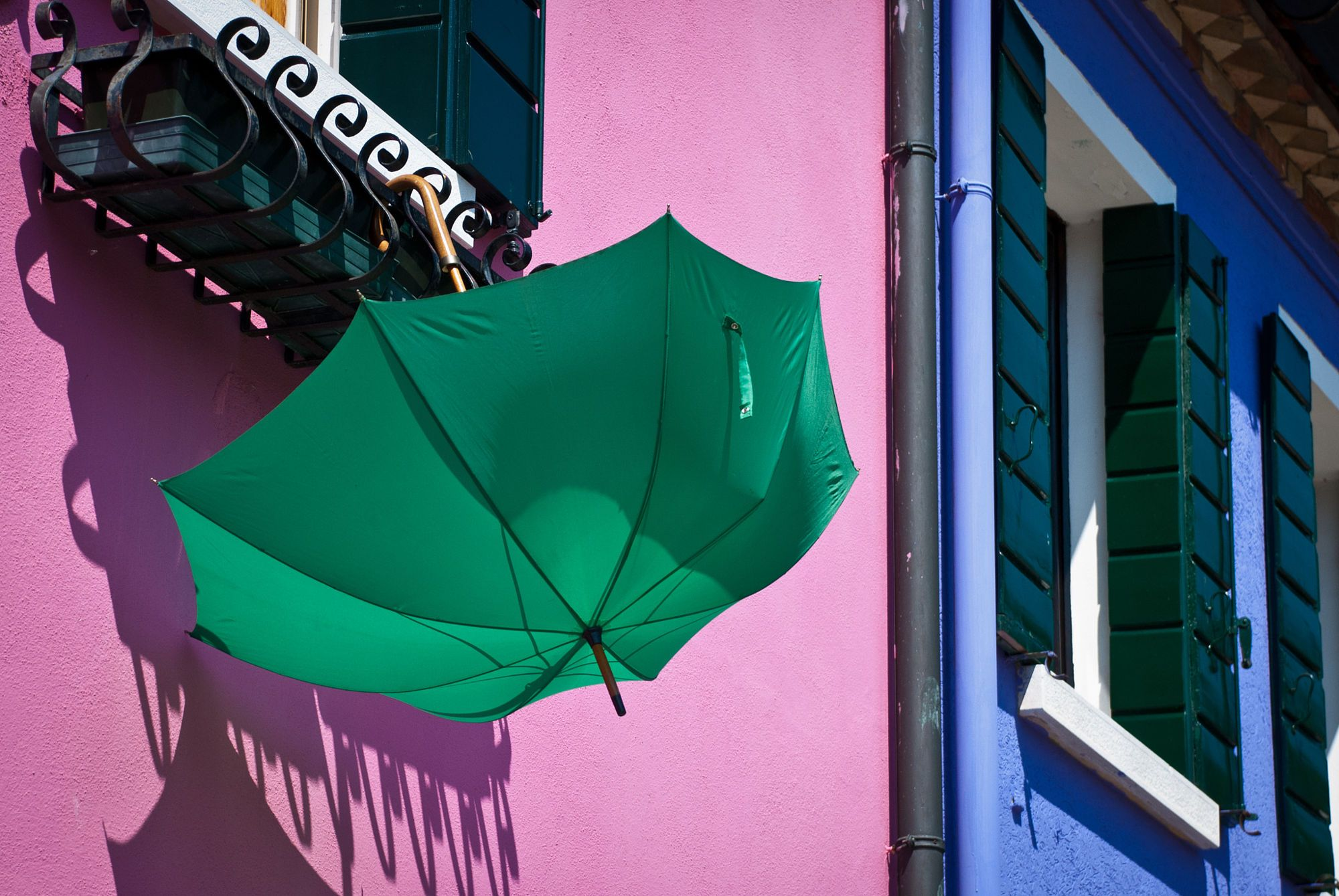 green umbrella hanging on balcony of colorful house   Paraplu ...