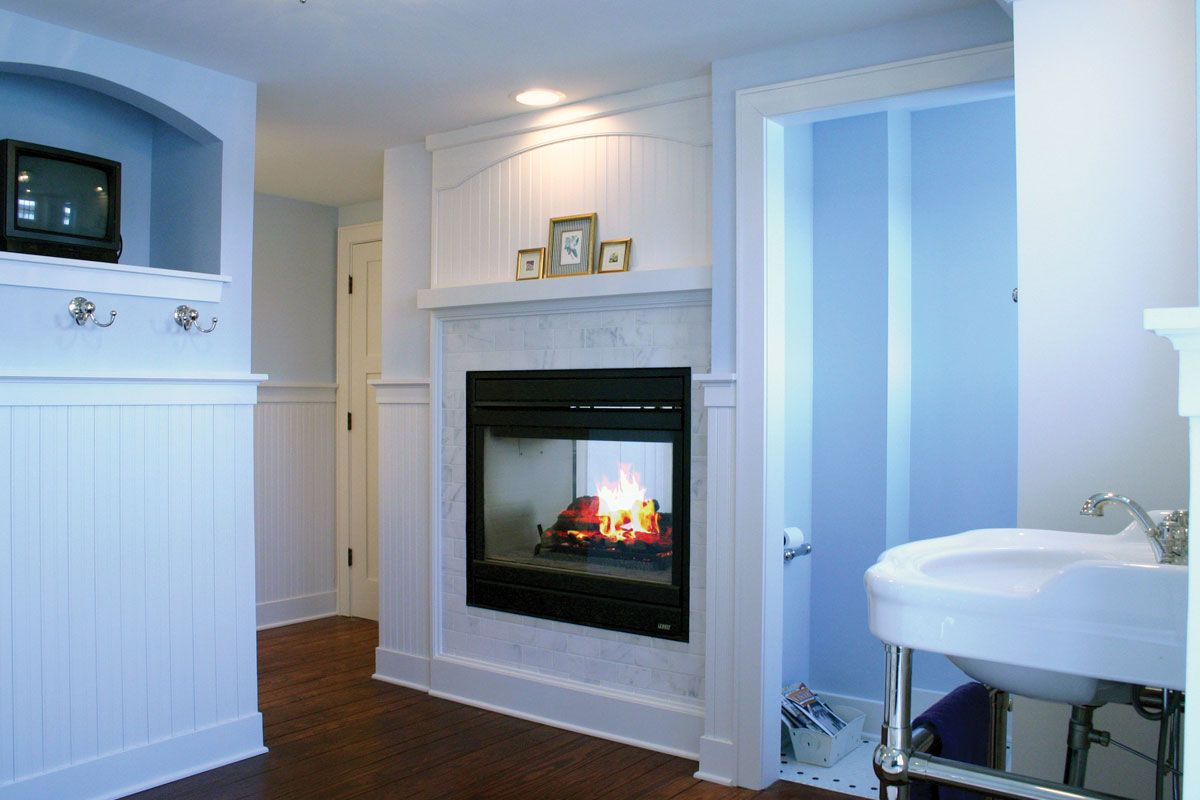 Master bathroom see through fireplace with white painted woodwork ...