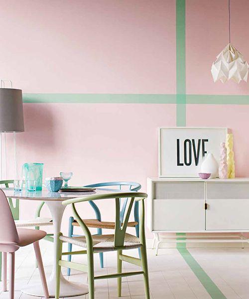 Comedor con pared rosa pastel y sillas en diferentes colores ...