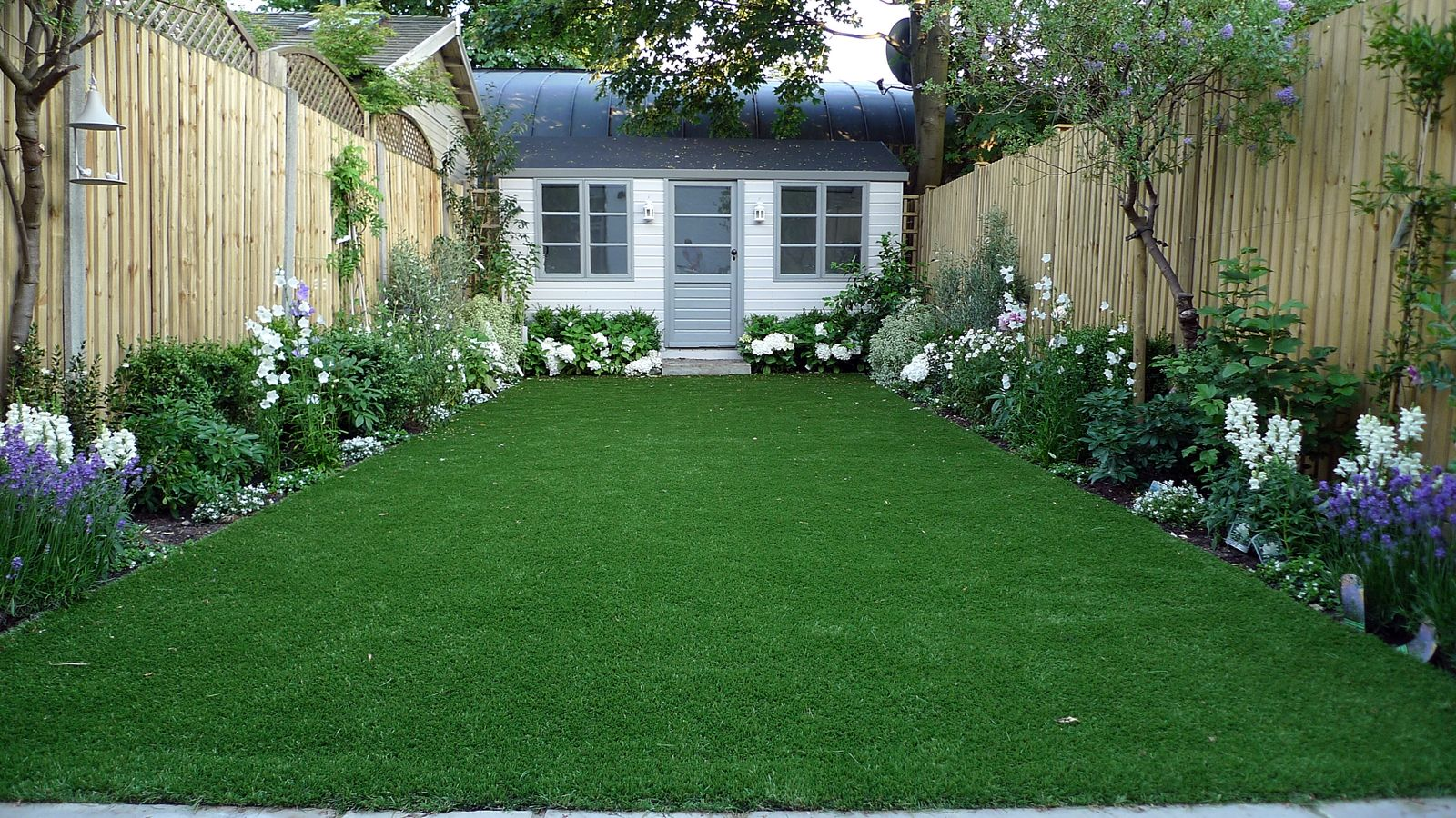 Artificial Easy Grass Lawn Summer House Sandstone Paving And White Flower Planting Scheme London Lond Backyard Landscaping Designs London Garden Garden Fence