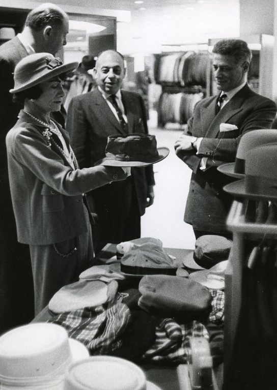 Chanel inspecting a hat on a visit to the Dallas outpost of luxury retailer Neiman Marcus, 1957