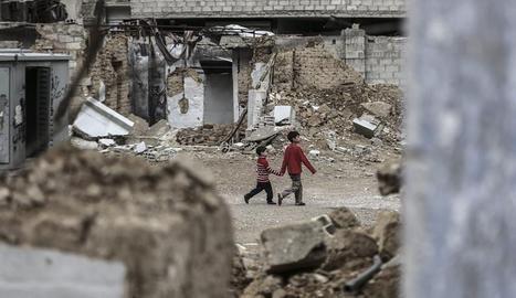 Dos niños sirios pasean entre los escombros de las afueras de la ciudad siria de Damasco.  EFE