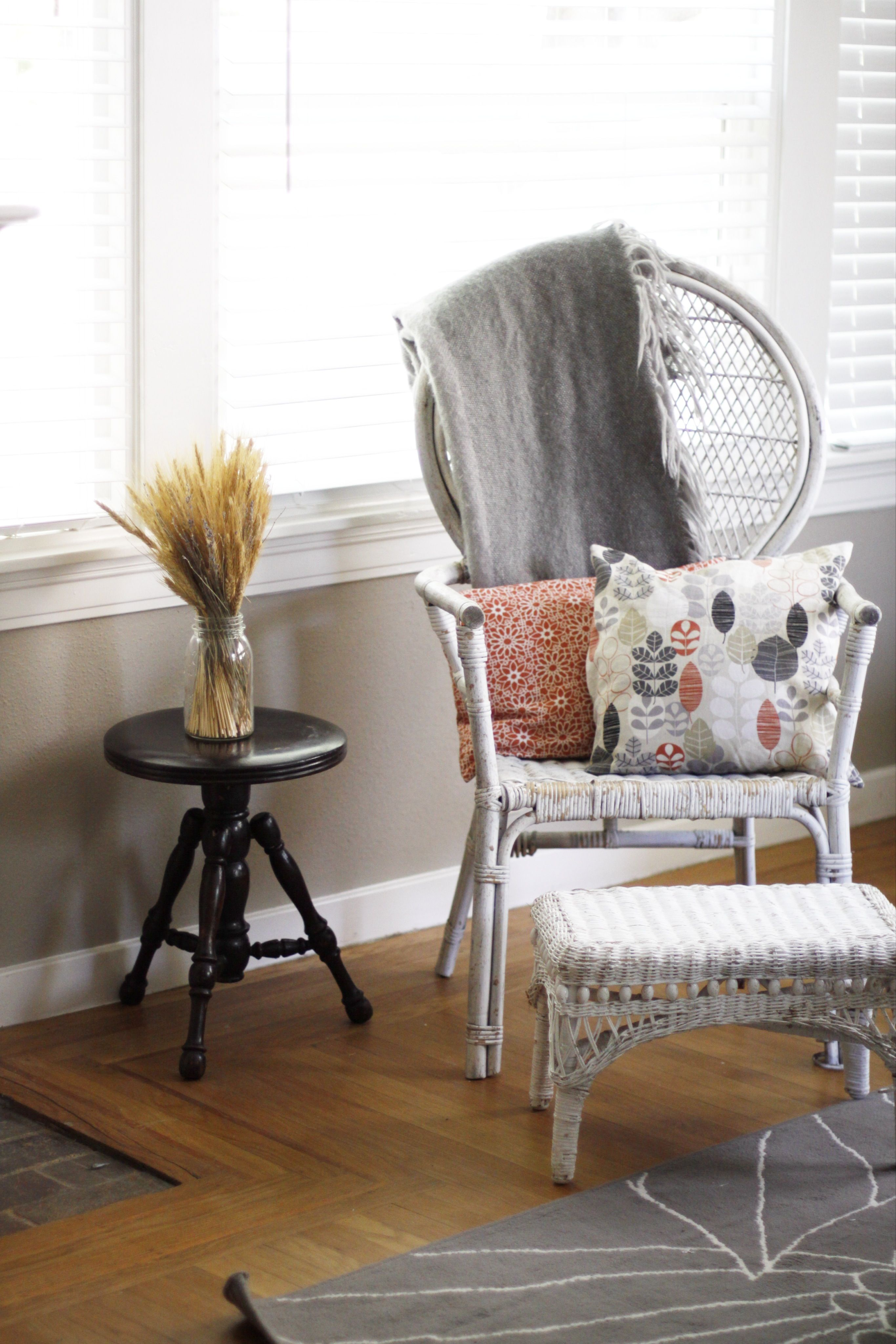 Use a stool as a side table. White wicker chair and foot
