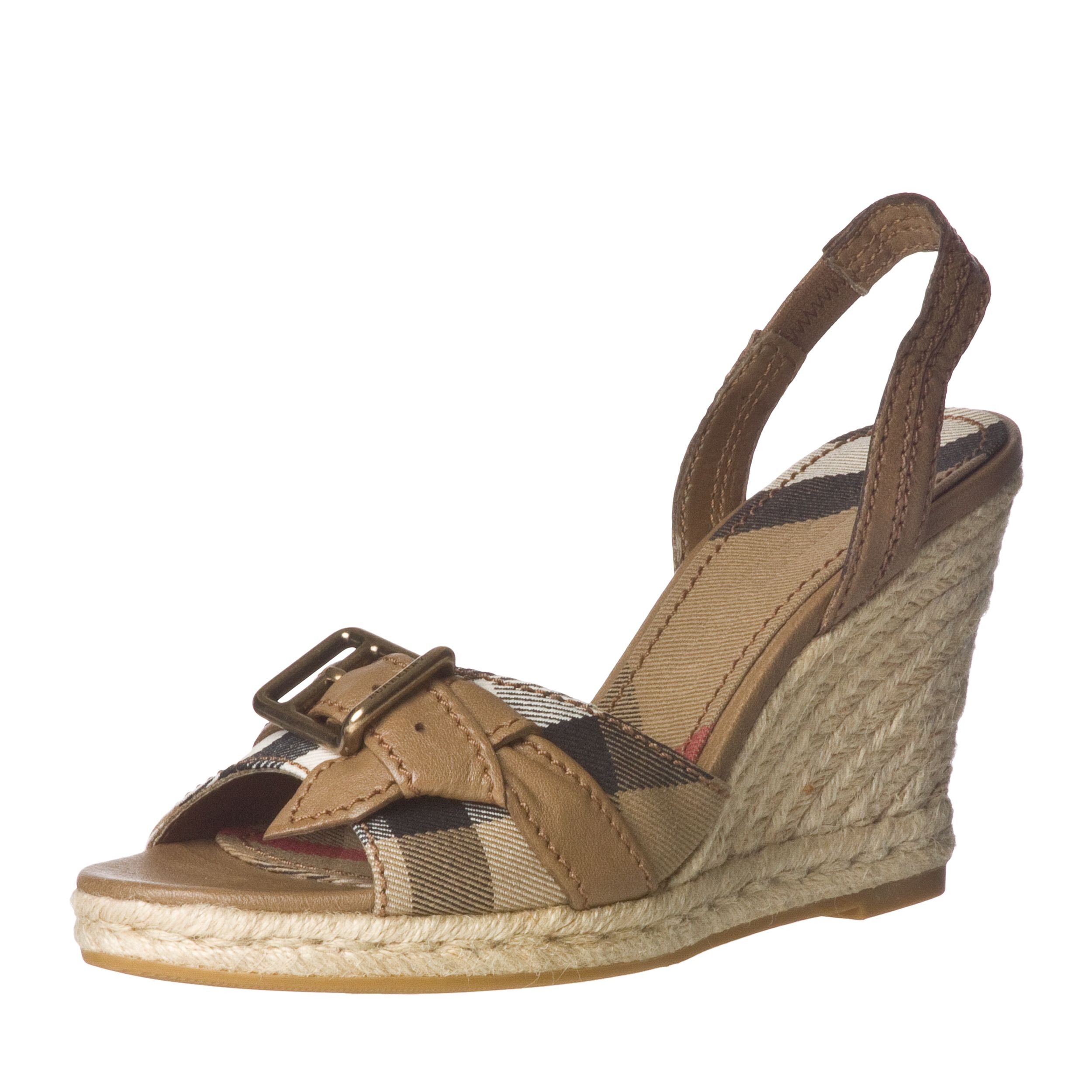 These designer sling-back wedges by Burberry feature a beautiful leather and cotton construction topped with a brass buckle. The 4-inch heel is covered in espadrille rope while the toe strap is printed with the signature check pattern.