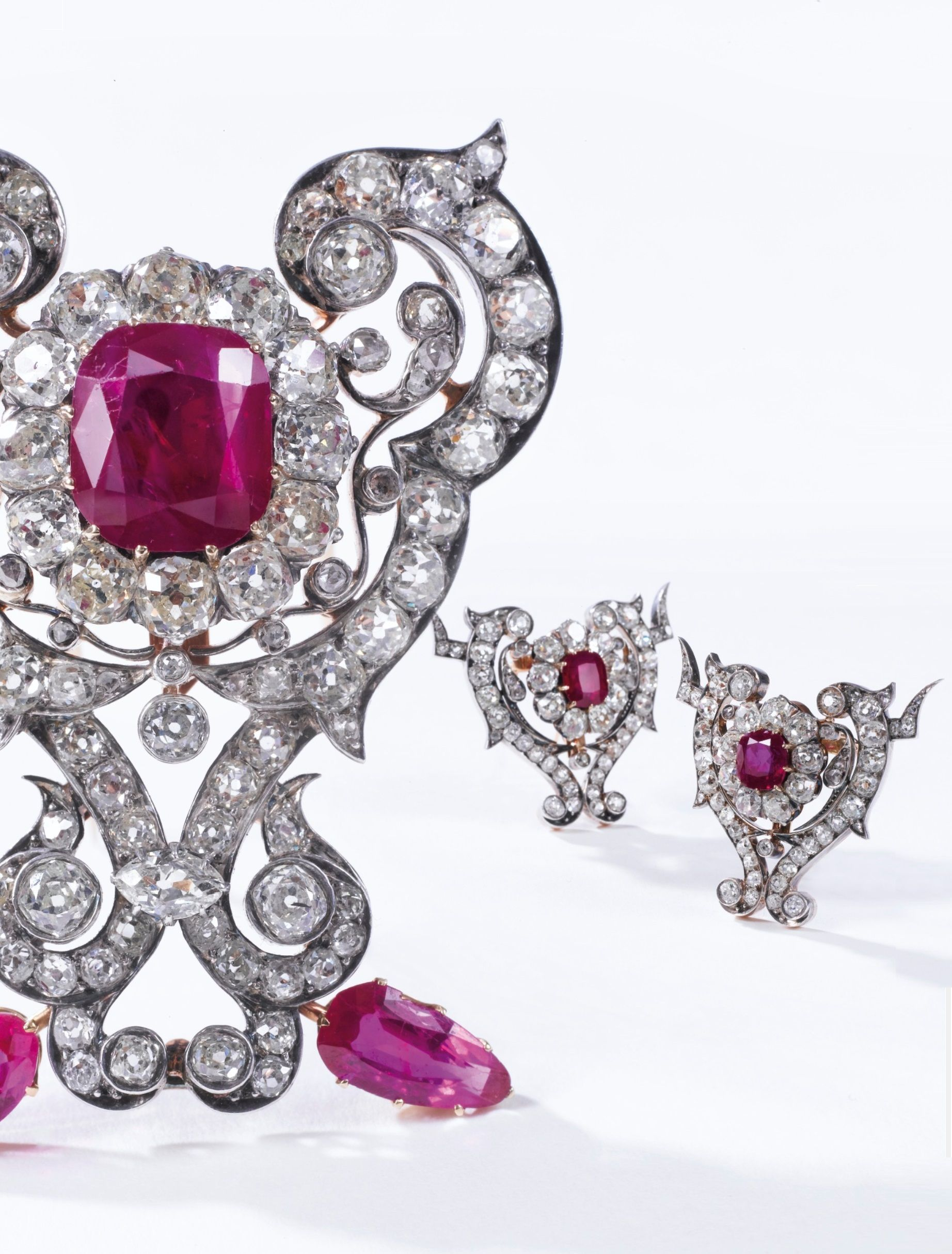 Three antique ruby and diamond brooches, late 19th century. Each of scroll design, set with cushion-, marquise-shaped, circular-, single-cut and rose diamonds, the largest brooch highlighted with a cushion-shaped ruby weighing 7.48 carats and pear- and marquise-shaped rubies, the two others set with a cushion-shaped ruby weighing 3.13 and 3.59 carats respectively, later brooch.