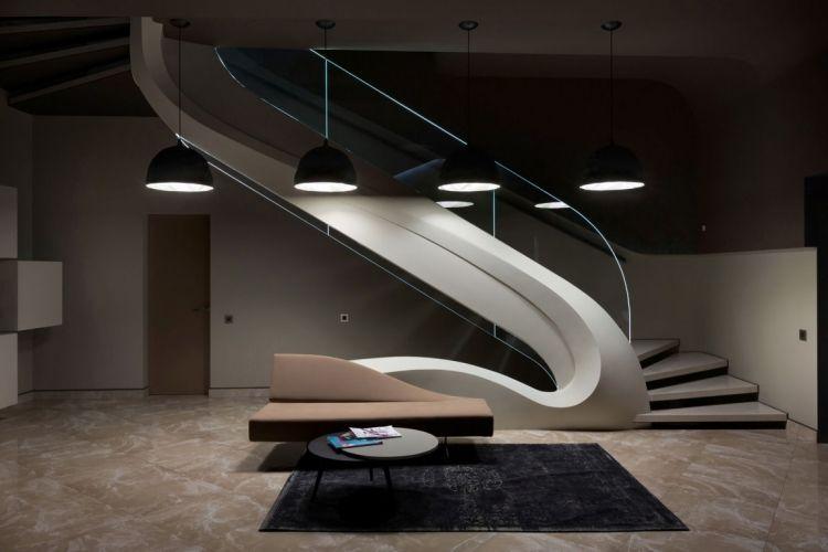 geschwungene Form und Glasgeländer der Innentreppe im Haus