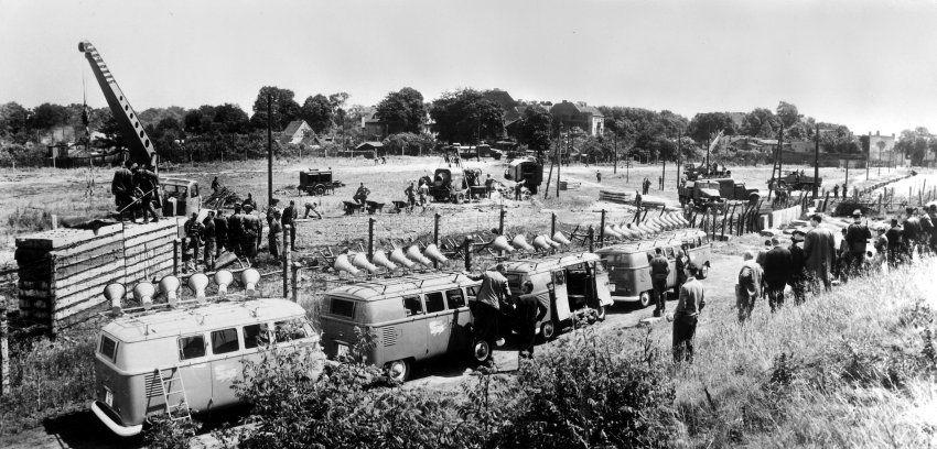 """Worte gegen Mauern: Fünf VW-Bullis des """"Studios am Stacheldraht"""" beschallen am 28. Juni 1962 aus nur wenigen Metern Entfernung DDR-Grenztruppen, die an der Klemkestraße in Berlin-Schönholz Grenzbefestigungen errichten. Regelmäßig sendeten die Wagen in ihren 15-minütigen Programmen auch Zitate aus der DDR geflohener NVA-Soldaten und Volkspolizisten. (Foto: ullstein bild - Gert Hilde)"""