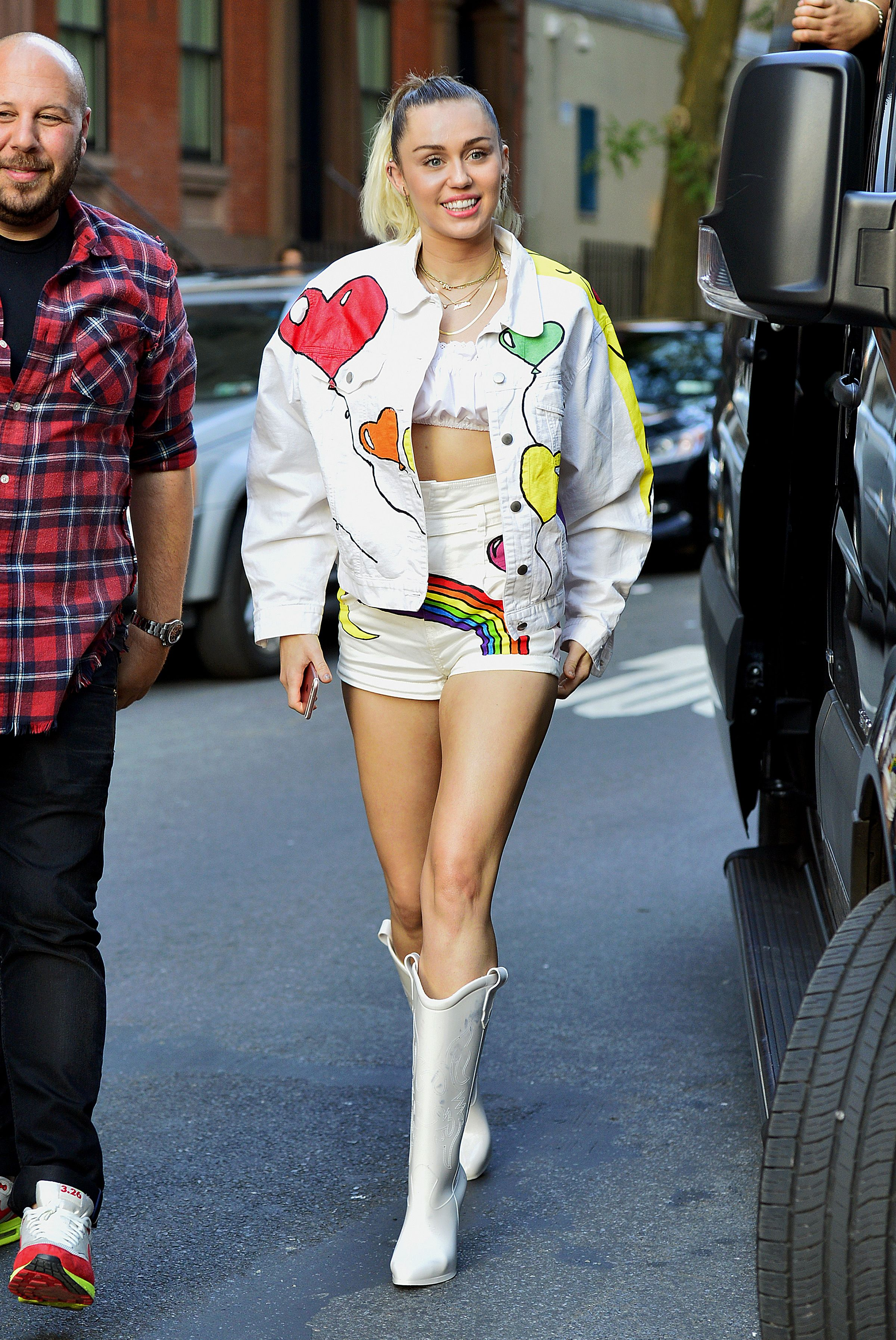 Miley Cyrus is all smiles looking stylish rocking a white denim ...