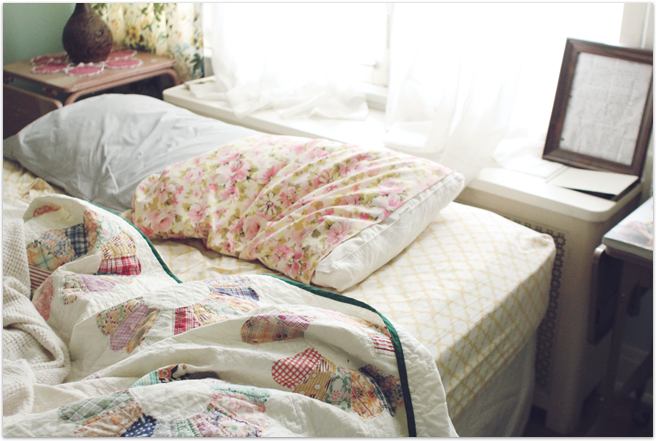 table behind bed in front of window. multicolored bedding/sheets. quilt. floral curtain + white. (tight space)