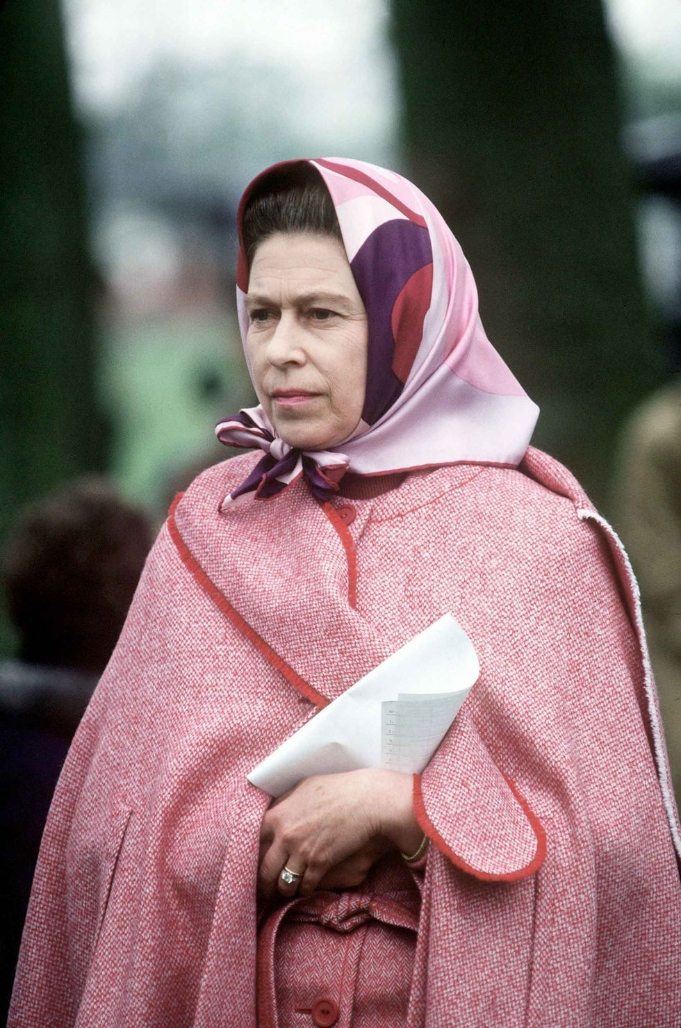 1979 The Queen stays warm in a red wool cape.