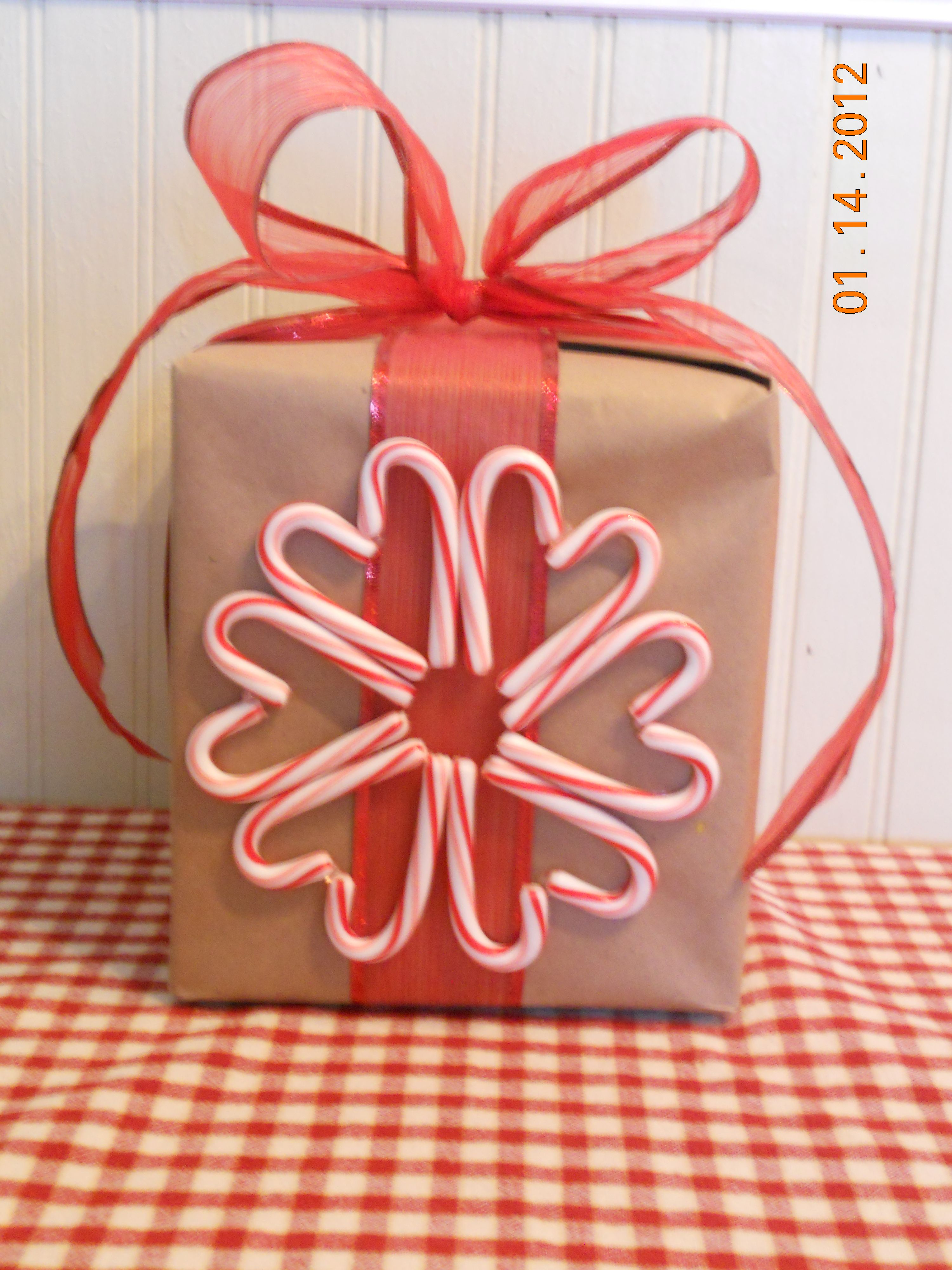 Make simple craft paper adorable gift wrap w/ pretty ribbon & a candy cane wreath! I also used candy canes in a heart shape & wrote who the gift was to and from inside it right on the paper.