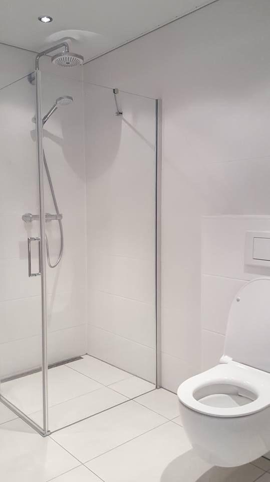 Een strakke badkamer met douche en toilet gerealiseerd door Sanidrome van Scheppingen uit De Kwakel.